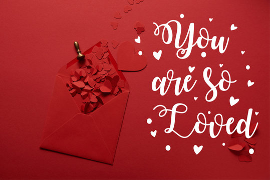 """top view of paper cut hearts and opened envelope on red background with """"you are so loved"""" lettering"""