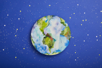 top view of planet picture on violet background with stars, earth day concept