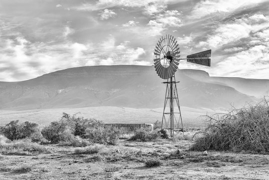 Landscape, with windmill and dam, in the Tankwa Karoo. Monochrome