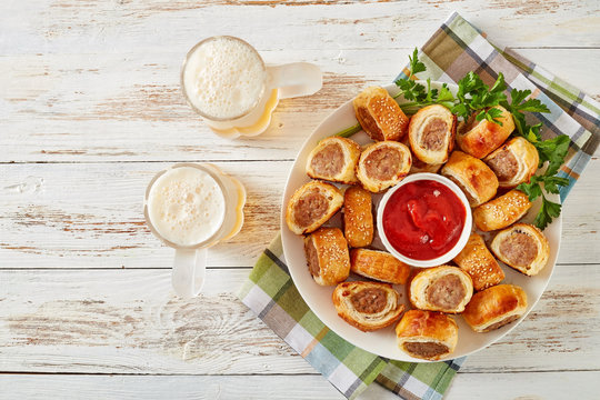 sausage rolls with tomato sauce and beer