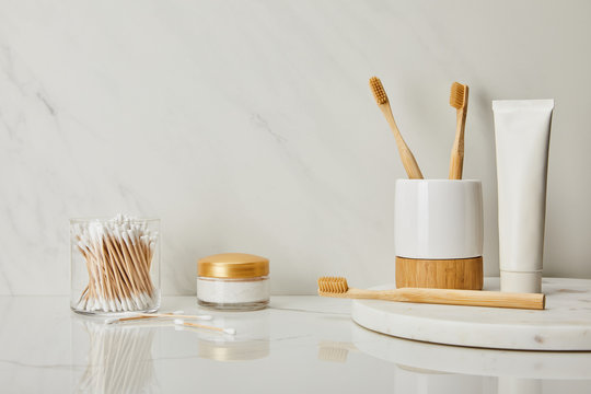 toothpaste in tube, holder, bamboo toothbrushes, cosmetic cream and ear sticks in glass on white marble background