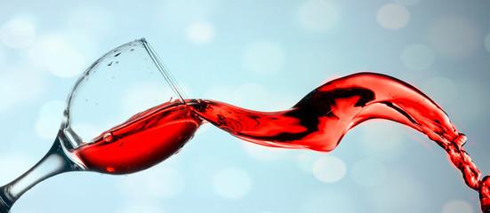 Red wine splash on blue bokeh background Fototapete
