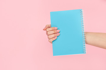 Crop hand showing blank blue notepad