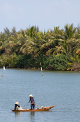 Fisherman with boat on River, Hoi An, Vietnam