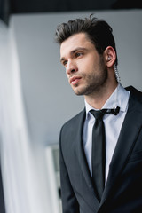 thoughtful bodyguard in suit with earphone