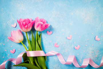 Spring holiday background. Flowers for Valentine's, Mother's or Women's Day. Pink tulips flowers on blue background. Top view, copy space