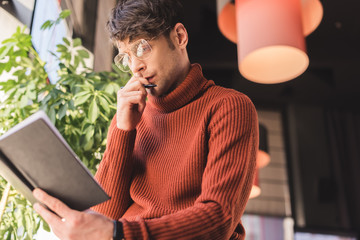 pensive man in glasses holding notebook while standing in cafe