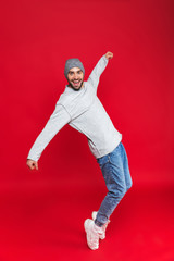 Full length image of happy man 30s with beard and mustache laughing while standing, isolated over red background
