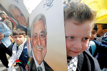 Palestinian boy holds a picture of president Mahmoud Abbas during a rally in support of Abbas in Nablus in the Israeli-occupied West Bank