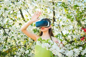 Stepping into the future. Cute girl play in spring garden. Young lady wear vr glasses in spring bloom. Innovative vr technology. Virtual technology simulation. Pretty girl in virtual reality headset