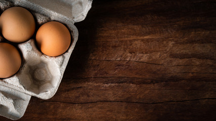 Fresh brown eggs in a carton box was placed on a wooden table to prepare food. Have copyspace to enter text. In aspect ratio 16: 9. Useful for health and easy to find according to the supermarket. Wall mural