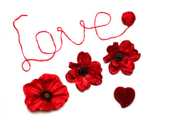 The word love is written in red thread on a white background. Red flowers and red box-heart on white background