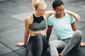 Two fit young women laughing together after a gym workout