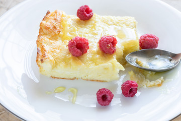 Close-up of piece of curd casserole with raspberries drizzled with honey and spoon on white plate.