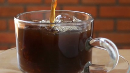 Fototapete - Pour hot coffee into a glass cup on the wooden table in Slow Motion