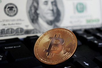 Bitcoin on a computer keyboard on the background of the US dollar, the symbol of electronic virtual money and the concept of cryptocurrency mining.