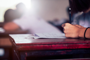 School student is taking exam and writing answer in classroom for education test concept