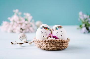 Zwei süße Ostereier im Osternest mit blauem Hintergrund und Blumen dekoriert - Textfreiraum oben