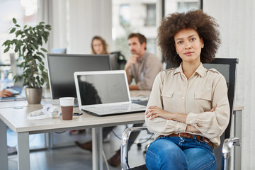 Mixed race CEO sitting at office and looking at camera. In background employees working.