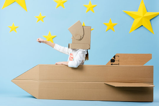 Kid in helmet sitting in cardboard rocket and holding fist up on blue starry background