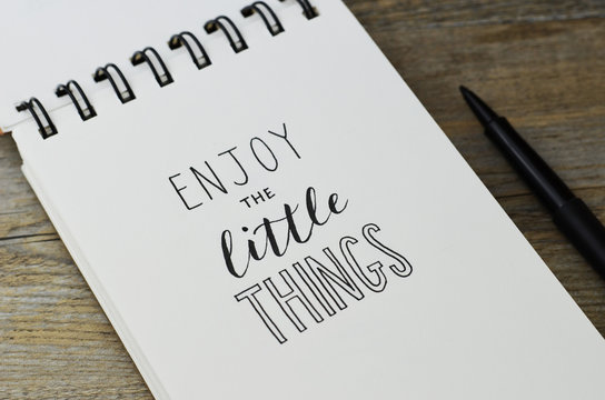 ENJOY THE LITTLE THINGS hand lettering in notebook with pen on wooden background