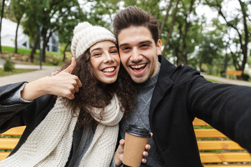 Happy young loving couple drinking tea or coffee outdoors in park talking with each other take a selfie by camera.