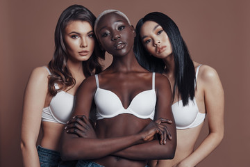 Too good to be real. Three attractive young women looking at camera while standing against brown background