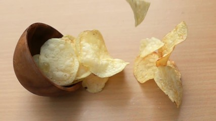 Fototapete - Potato chips fall down to the wooden table in Slow Motion