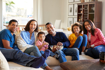 Mixed race, three generation family sitting on sofa in the living room together, eating popcorn and looking to camera, close up