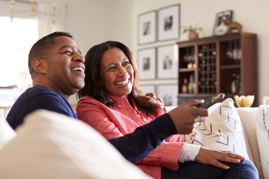 Close up of middle aged couple sitting on the sofa in their living room using remote and watching TV, laughing, close up