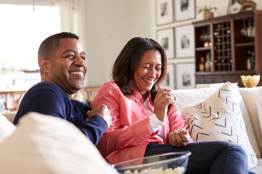 Close up of middle aged couple sitting on the sofa in their living room watching TV, laughing and eating popcorn, close up