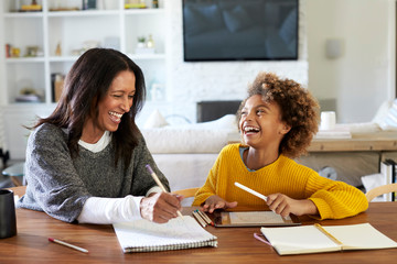 Middle aged mixed race woman sitting at a table in the dining room doing homework with her granddaughter, both laughing, close up
