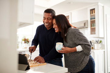 Middle aged mixed race couple standing at worktop in the kitchen preparing food following a recipe on a tablet computer, selective focus