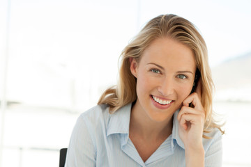 woman on the phone at workplace - beautiful businesswoman using smartphone for a call