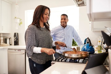 Middle aged mixed race couple standing together in the kitchen preparing food on the hob using a recipe on a tablet computer, selective focus