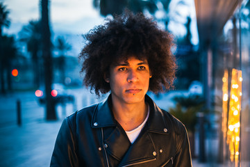 Serious looking young afro american man illuminated by showcase light in the street