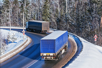 Freight trucks move on the road at winter day time.