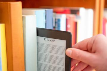 Hand of student keeping digital tablet in bookshelf in school library