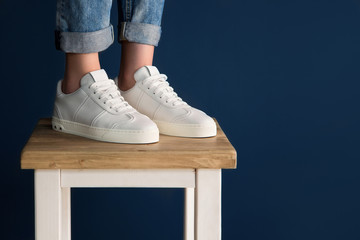 White sneakers on the legs of the girl. Girl in jeans and white sneakers.