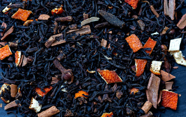 Dry tea with fruit and flower petals as background top view