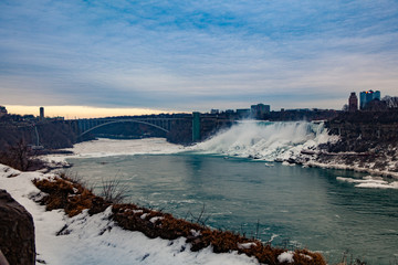 Niagara Falls CANADA - February 23, 2019: Winter frozen view at the Rainbow bridge, steel arch bridge connecting the United States and Canada