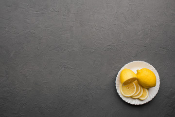 Fresh sliced lemons in white plate on dark stone background. Copy space. Top view.