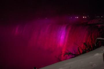 Niagara Falls CANADA - February 23, 2019: Beautiful night Winter frozen idyll at Horseshoe Falls illuminated with colorful lights, the Canadian side of Niagara Falls