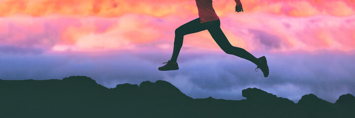 Running legs silhouette of athlete runner woman trail running on mountain rocks against pink sunset sky background. Panoramic banner.