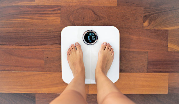 Woman bare feet standing on a digital scale with body fat analyzer that uses bioelectrical impedance (BIA) to gauge the amount of fat in your body