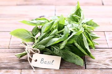 Green basil leafs with paper card on brown wooden table
