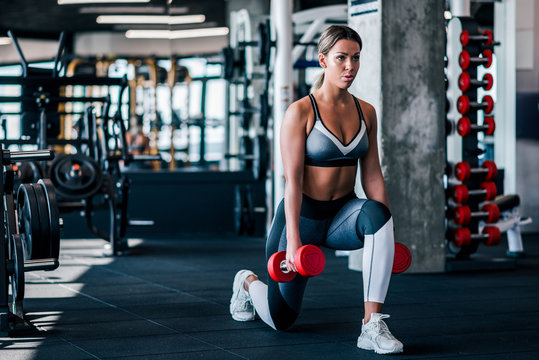 Young muscular woman doing Lunges exercise with dumbbells in the gym.