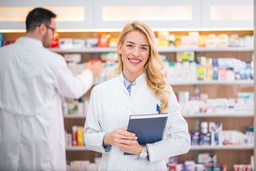 Portrait of a smiling female pharmacist, male colleague working with drugs in the background.