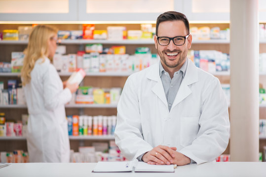 Portrait of a handsome pharmacist at the counter of a drugstore, female colleague working in the background.
