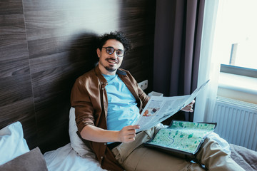 smiling traveler with map holding newspaper in hotel room